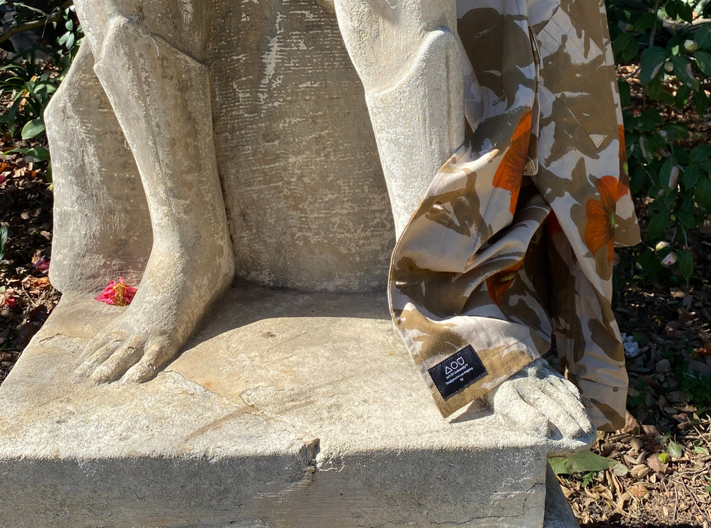 Statue with Art Of Uniformity Desert Poppy upcycled military jacket draped across the foot.