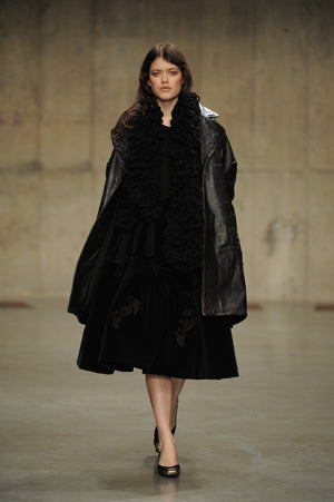 Claire Barrow Autumn/Winter 2013 Look 10 Black leather oversized coat, hand knitted scarf and velvet embroidered skirt