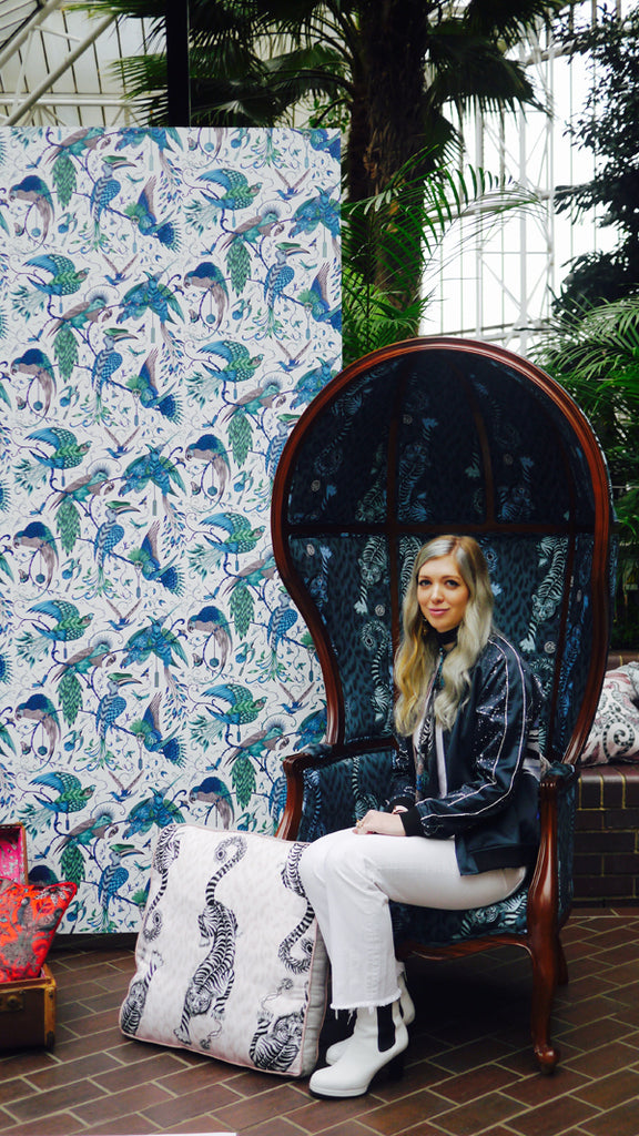 Left: Emma proudly posing amongst her hand-drawn designs adorning wallpaper, and fabrics covering cushions, chairs and even suitcases. Right: The wallpaper samples truly stood out amongst the great foliage within the Barbican Conservatory.