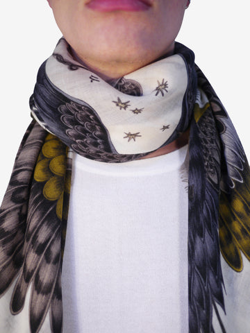 The scarf features vibrant, fantastical birds in flight, set upon a stylish colour of gold and yellow.