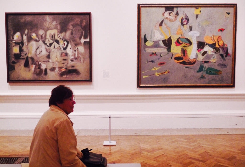 A visitor taking in the surrounding works of Arshile Gorky.