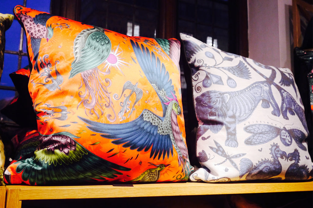 The new Phoenix Printed and Extinct Jacquard Woven square cushions are displayed on the shelves in Liberty.