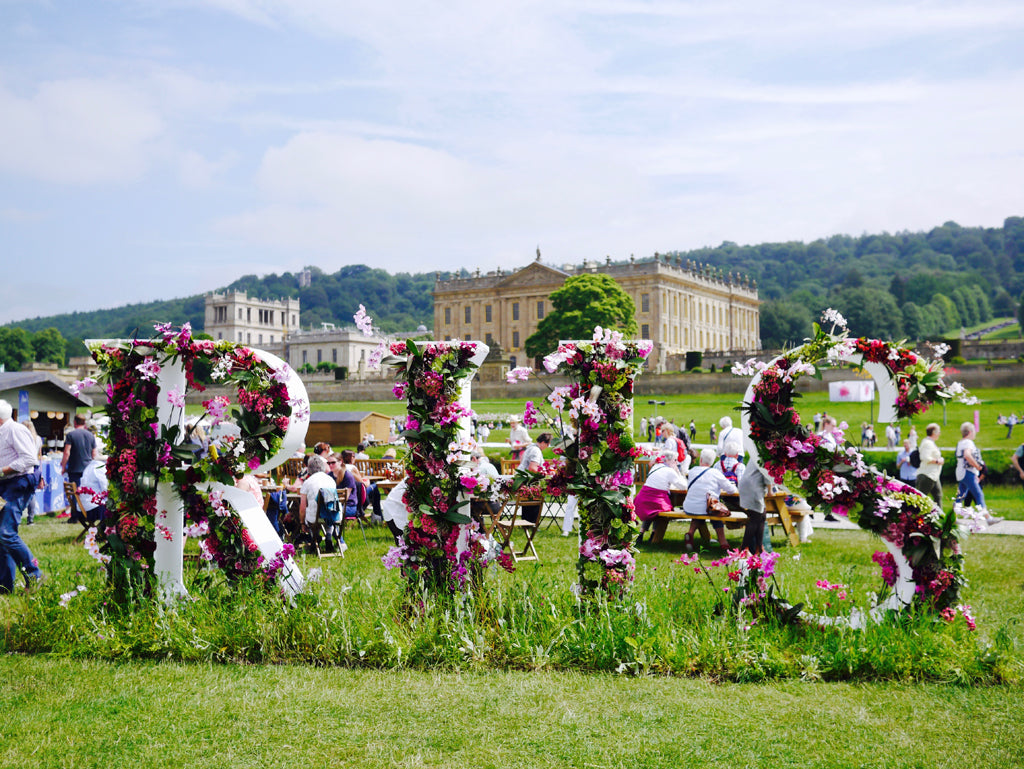 The RHS logo filled with beautiful cerise flowers
