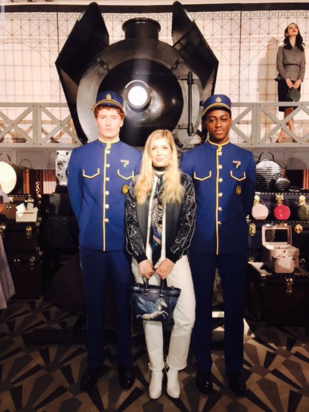 Left: Emma posing with two train porters outside the replica Orient Express. Right: Emma proudly displaying her design for Aspinal's Murder on the Orient Express collection.