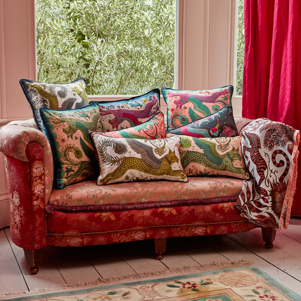A sofa adorned with Emma J Shipley Silk cushions including the magenta square cushion, they're perfect for layering on a bed or sofa or on their own, they're a magical addition to any home