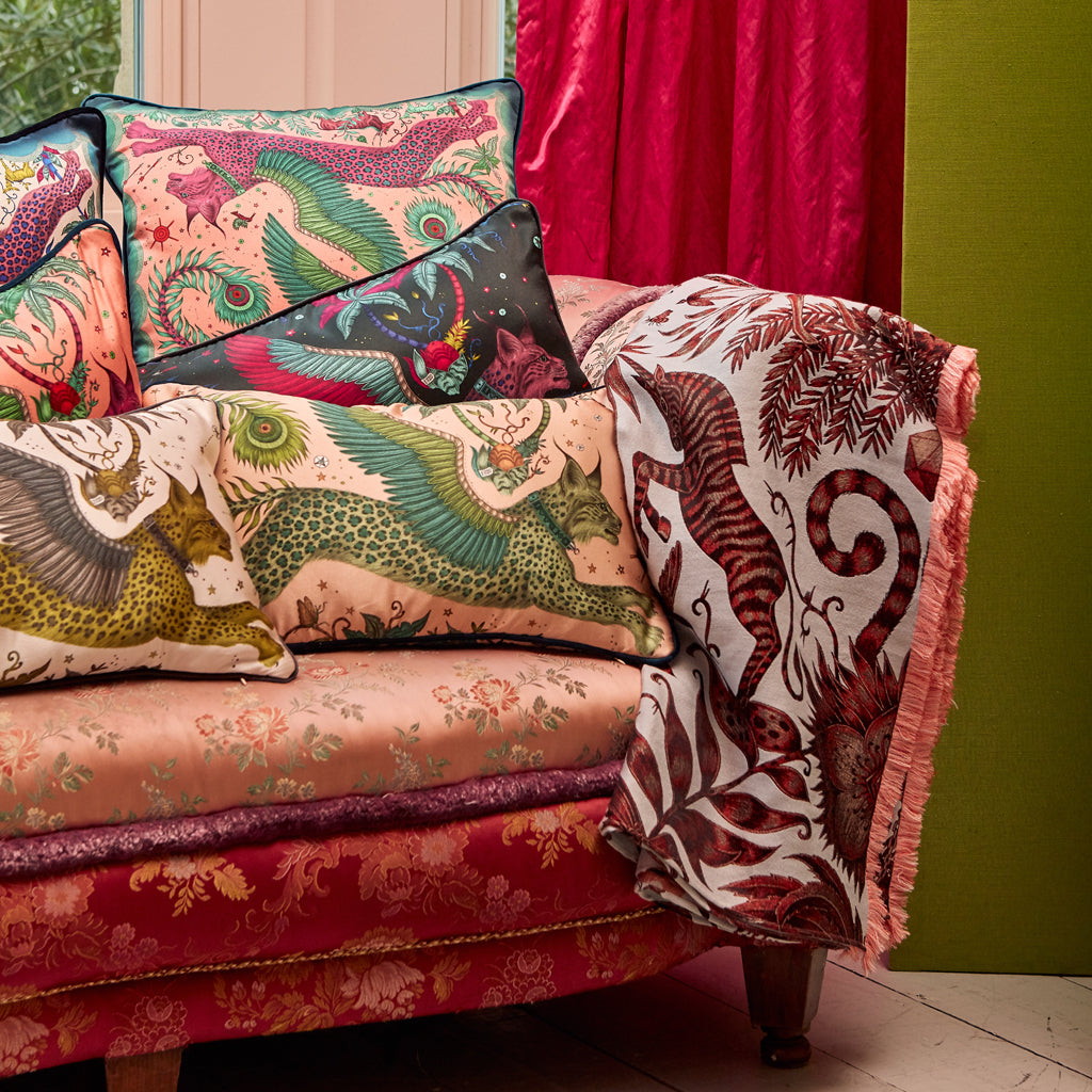 A close up of the lynx silk cushions all layered to create a fantasy themed interior, the magenta square cushion is the perfect treasure for any home interior.