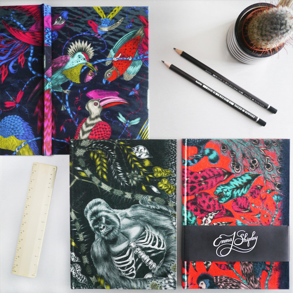 A lifestyle shot of the Emma J Shipley silk sketchbook collection, featuring the Audubon, Silverback and Amazon designs.