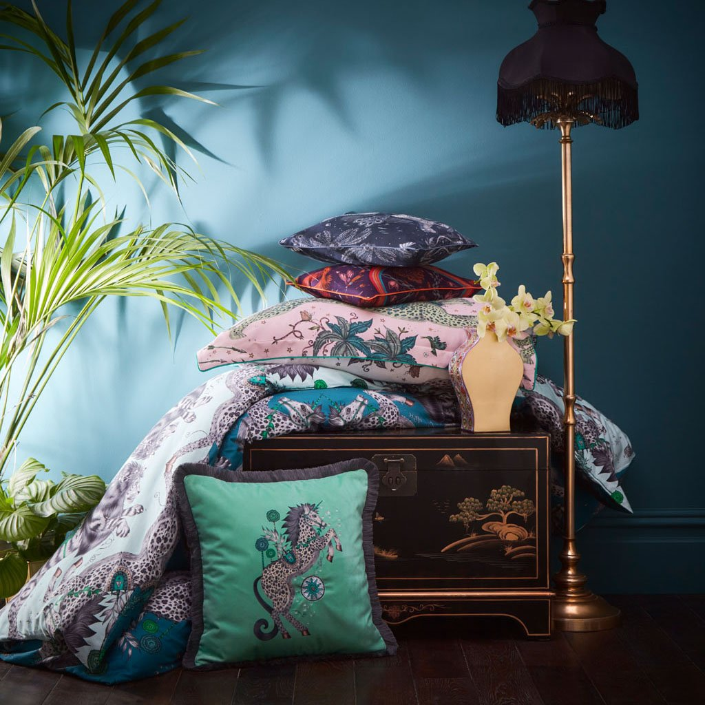 A stack of cushions that are all part of the new Emma J Shipley bedding range with Clarke & Clarke featuring some of her most popular designs such as Zambezi and Lynx as well as this Caspian Velvet fringed Cushion Aqua.
