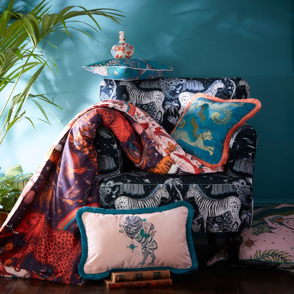 A Lost world Navy Velvet Chair with Wine Zambezi Bedding draped over it, along with a Caspian bolster Cushion, Lynx Square Velvet Cushion and a Caspian Boudoir pillowcase in Teal