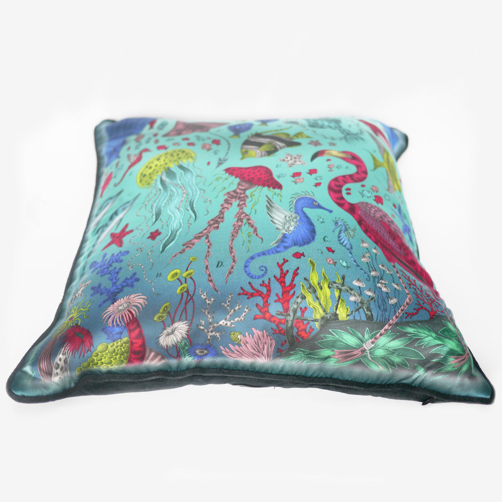 Bright turquoises and blues are highlighted amongst bright coral on this luxurious silk and cotton printed cushion.