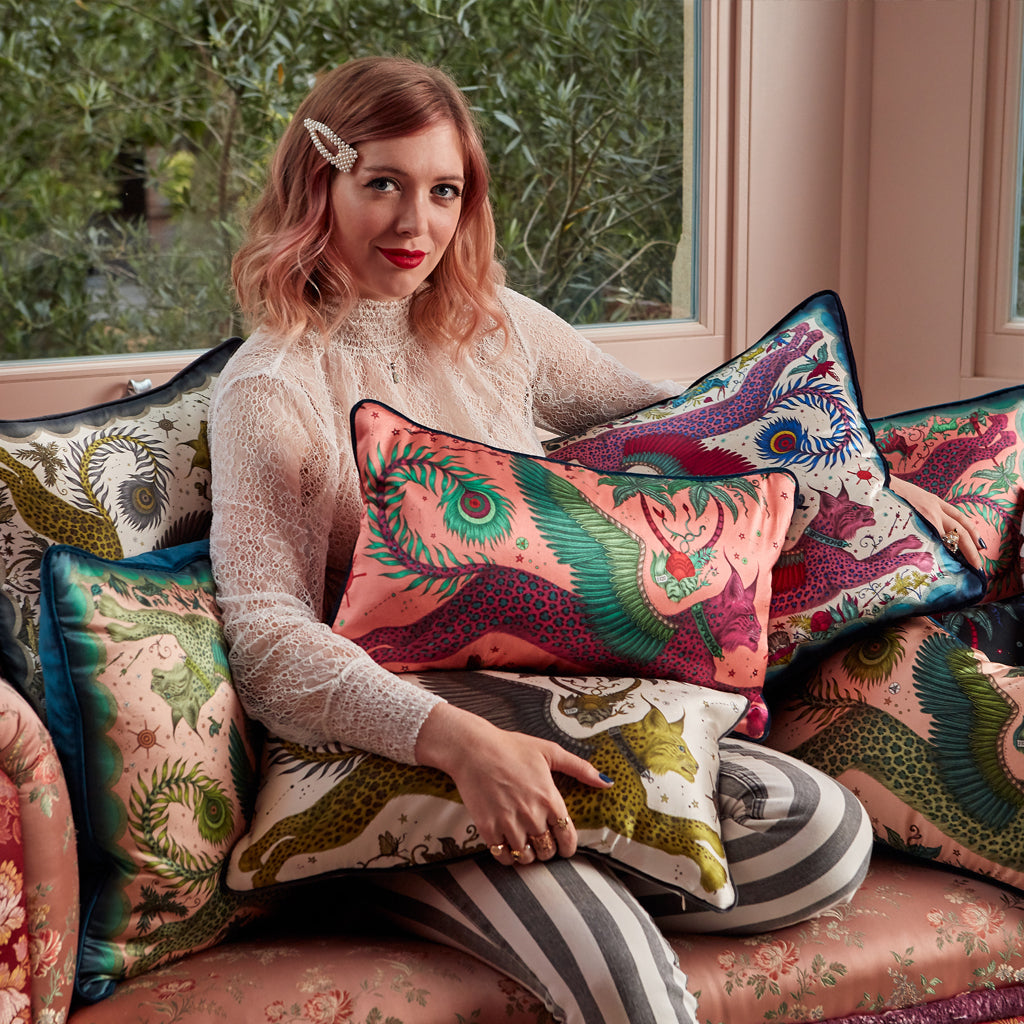 Emma J Shipley holding the Magenta Bolster cushion along with a selection of the Lynx cushions from the range, the Magenta Bolster cushion pairs perfectly with all the other colour-ways or can add animal magic to any chair, sofa or bed.
