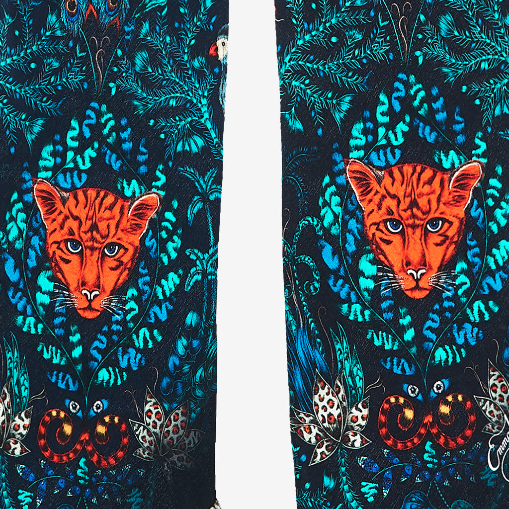 The hand-drawn design features jaguars hidden amongst foliage and playful parrots with peacock tails.