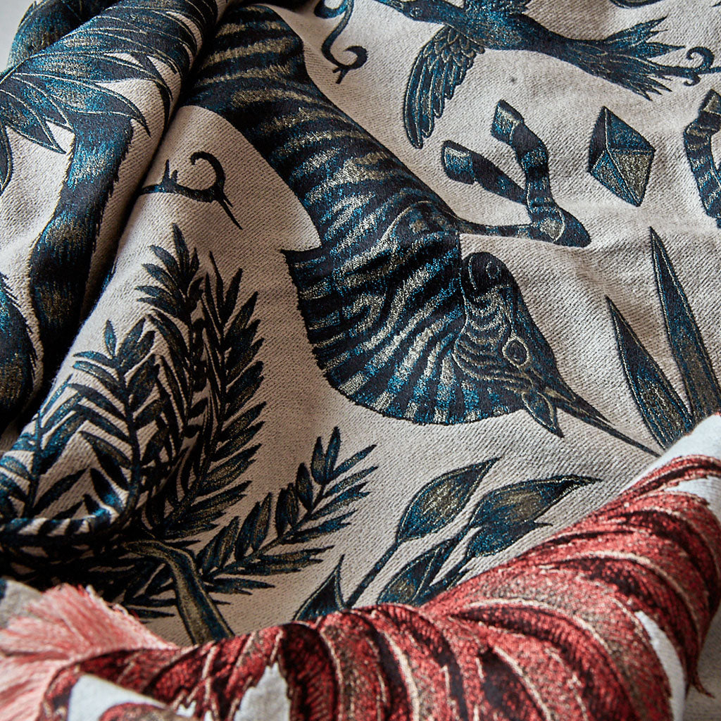 Detail of Emma J Shipley jacquard woven luxury silk and wool throw blankets, in the Kruger design, in Teal and Coral colours