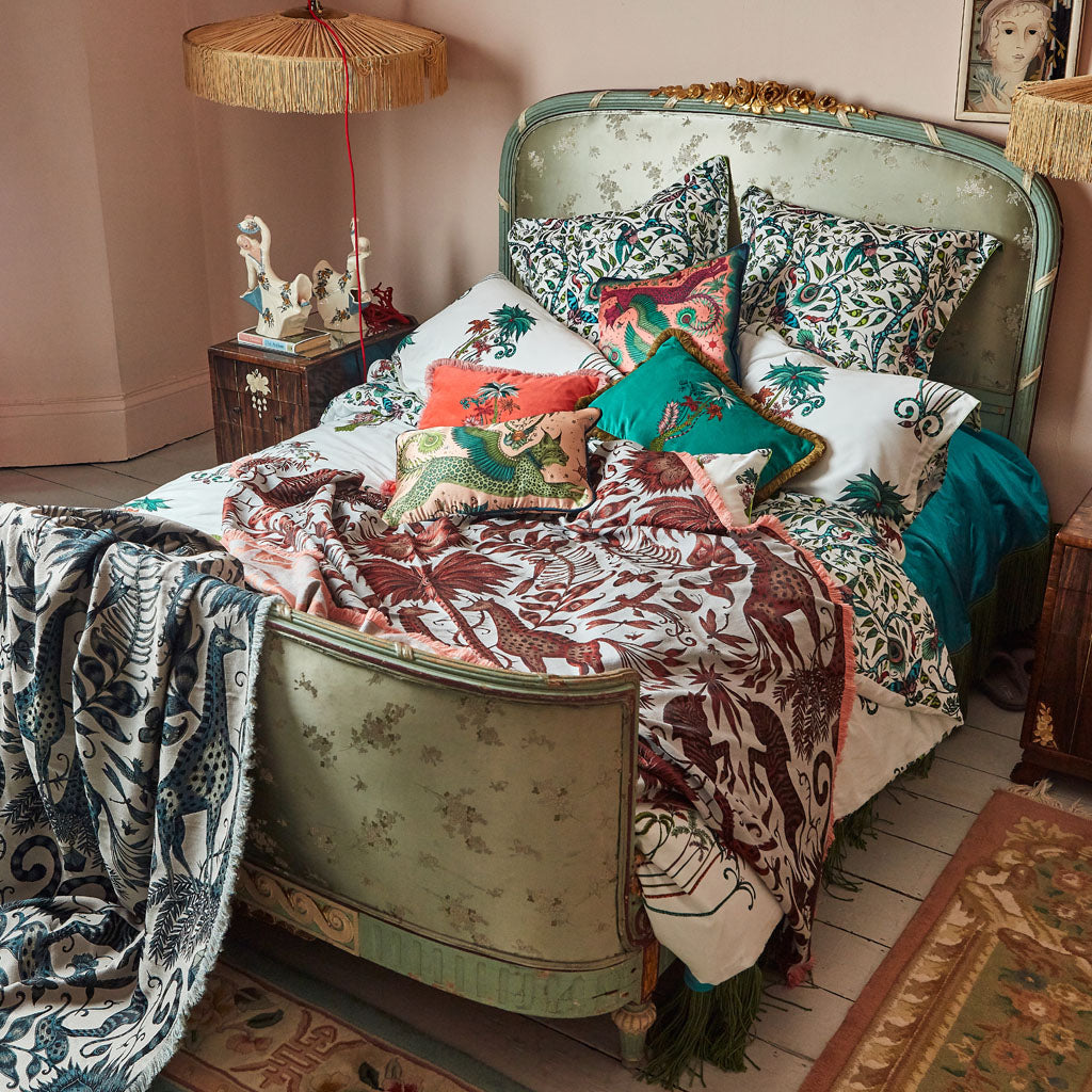 Emma J Shipley interior setting featuring luxury throws, jungle bedlinen and velvet cushions and pillows