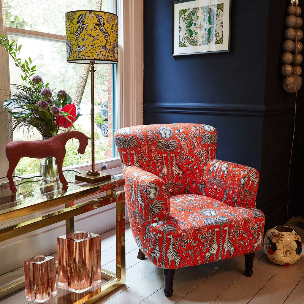 Kruger Dalston Armchair shown in a living environment, the striking red colour way stands out and the animal print evokes an african safari