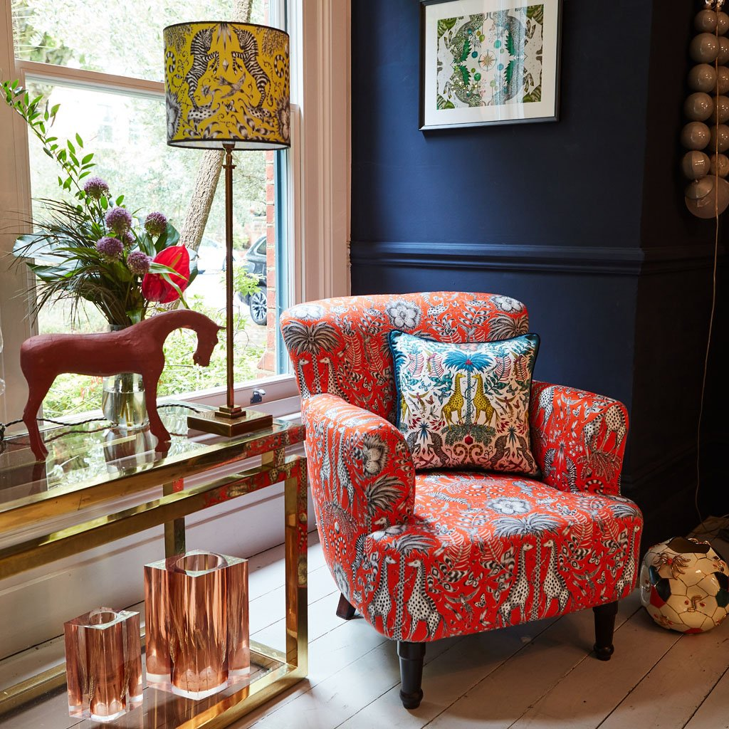 Maximalist interior featuring Emma J Shipley's Kruger red armchair and small lampshade with zebras