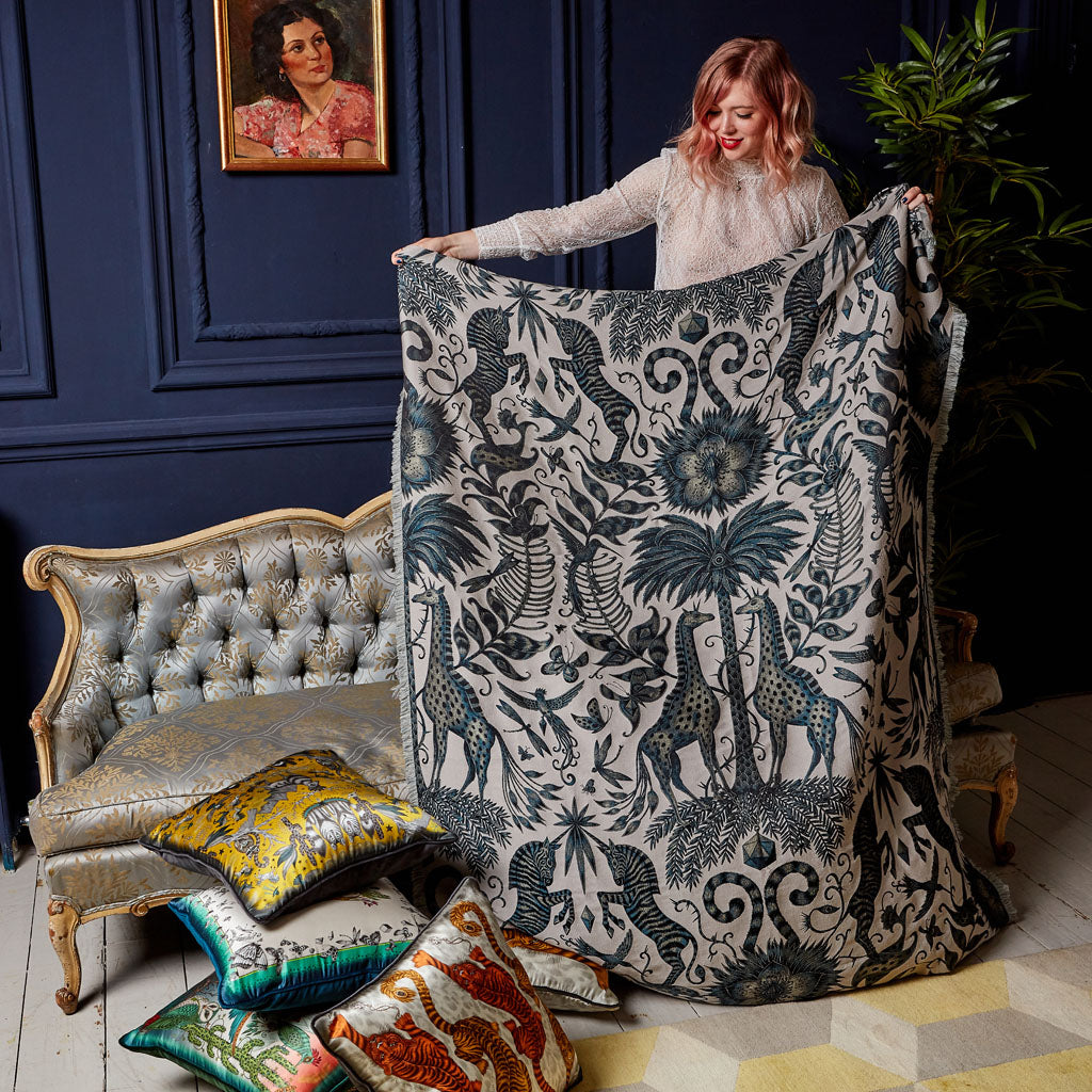 Emma J Shipley holding a Kruger throw, inspired by African nature, woven in Italy in silk and wool, for a cosy and luxury feel