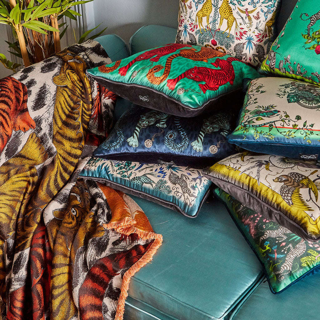 Detail of an Emma J Shipley designer luxury throw with stacks of silk cushions with animal inspired designs.