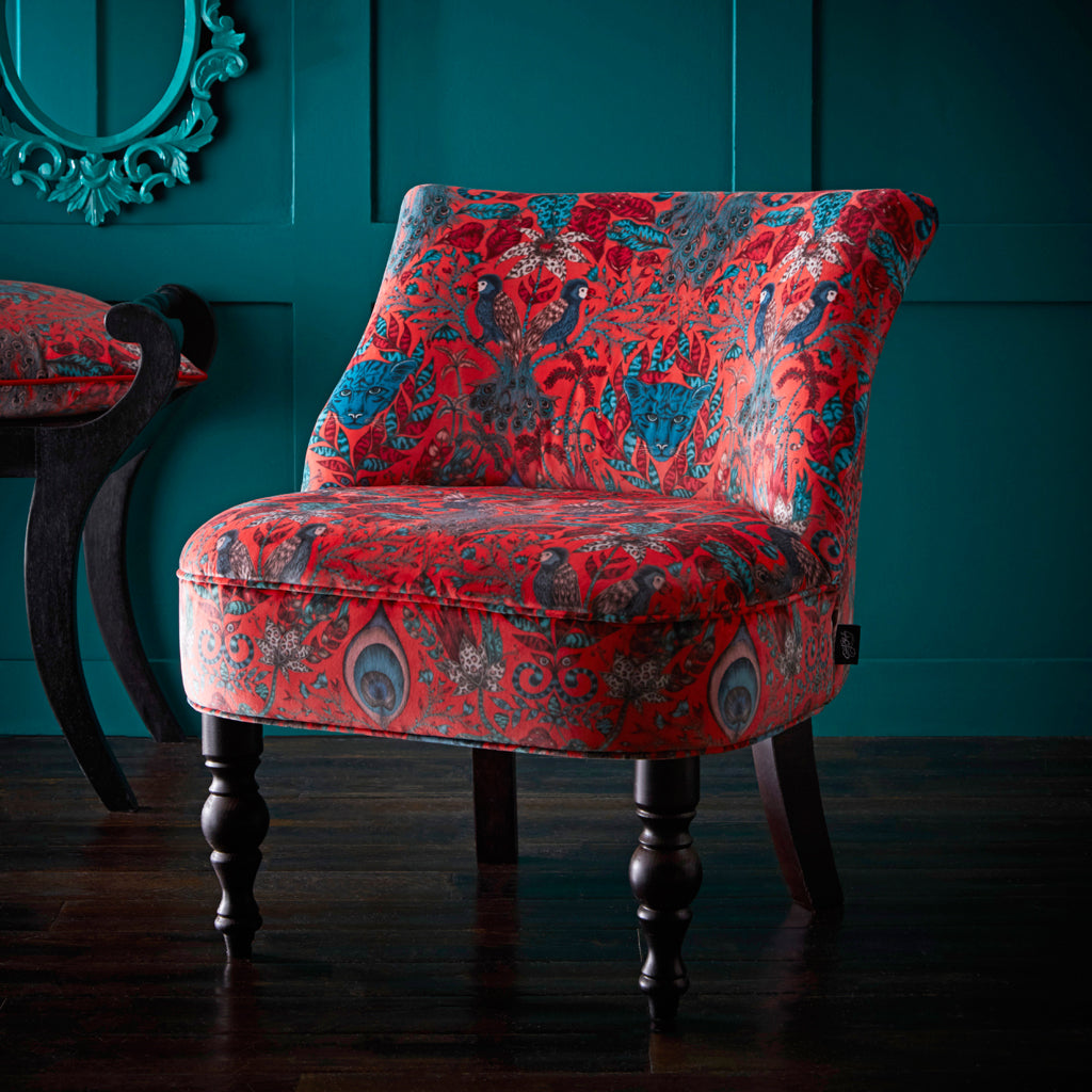 The red velvet Amazon Langley Chair is designed by Emma J Shipley in collaboration with Clarke & Clarke. It features a playful scene inspired by the jungle upon a striking velvet fabric background