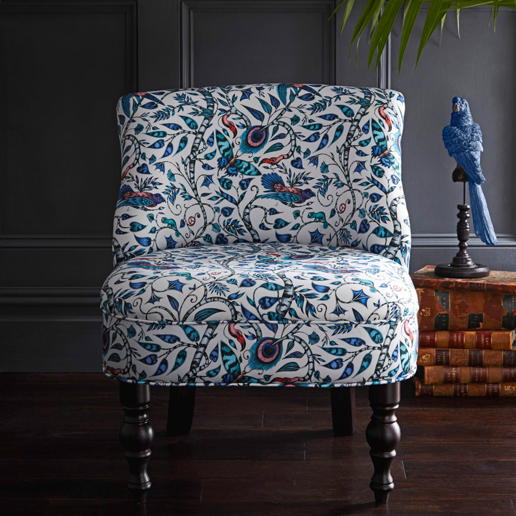 Exotic birds, creatures and foliage twist around each other in this bold occasion chair designed by Emma J Shipley for Clarke & Clarke