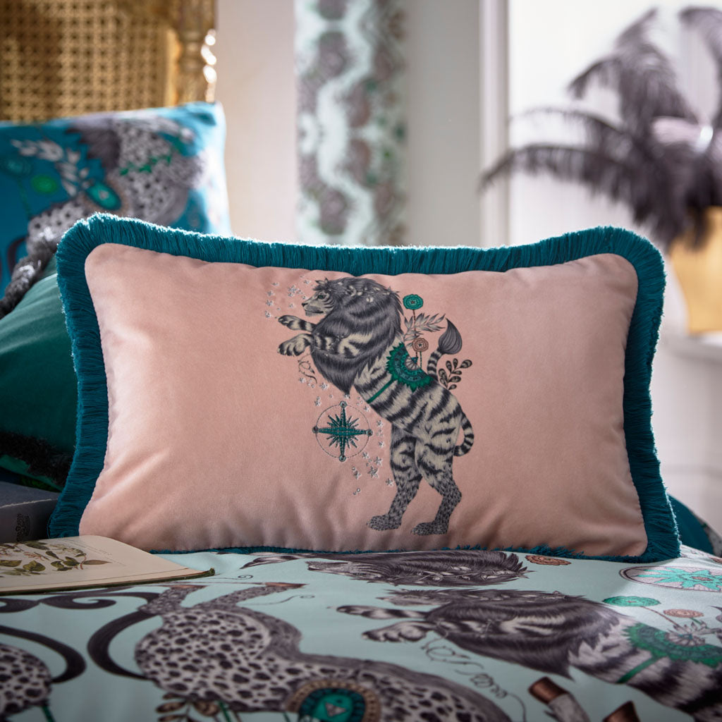 Transform your bedroom into a surreal Narnia inspired dream with the Caspian Bolster Cushion in blush, designed by Emma J Shipley. Featuring a striking English Lion deep teal fringing all inspired by the Chronicles of Narnia.