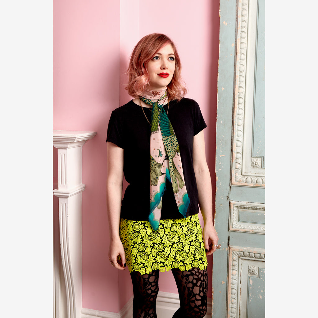 Emma J Shipley wearing the luxurious Lynx silk skinny scarf in an imaginative palatte of tonal pink and a range of greens