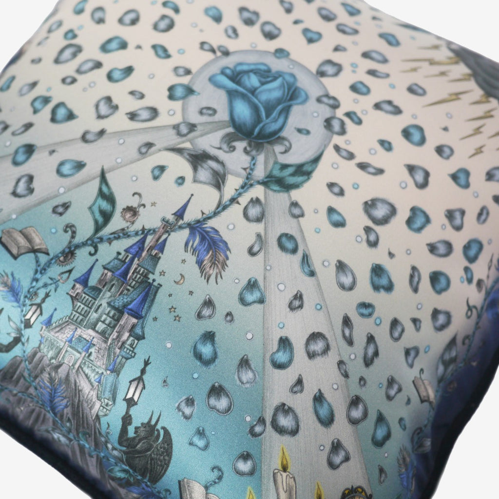 Detailed image of the enchanting castle featured on the Emma J Shipley Silk and Cotton printed cushion in Blue, complete with the cursed rose and petals.