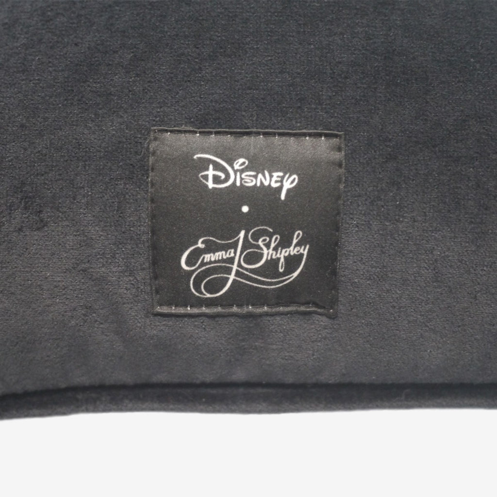 The luxurious black velvet backing of the Emma J Shipley Cotton and Silk Beauty and the Beast Cushion, complete with a Disney x Emma J Shipley logo label at the bottom.