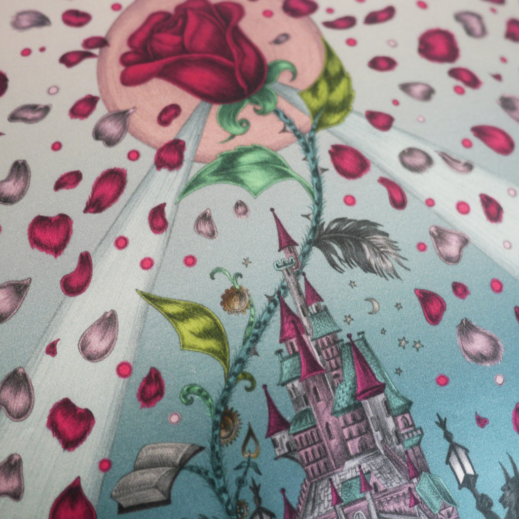 Detailed image of the enchanting castle, cursed rose and petal illustrations featured on the Disney x Emma J Shipley Beauty and the Beast cushion in Magenta.