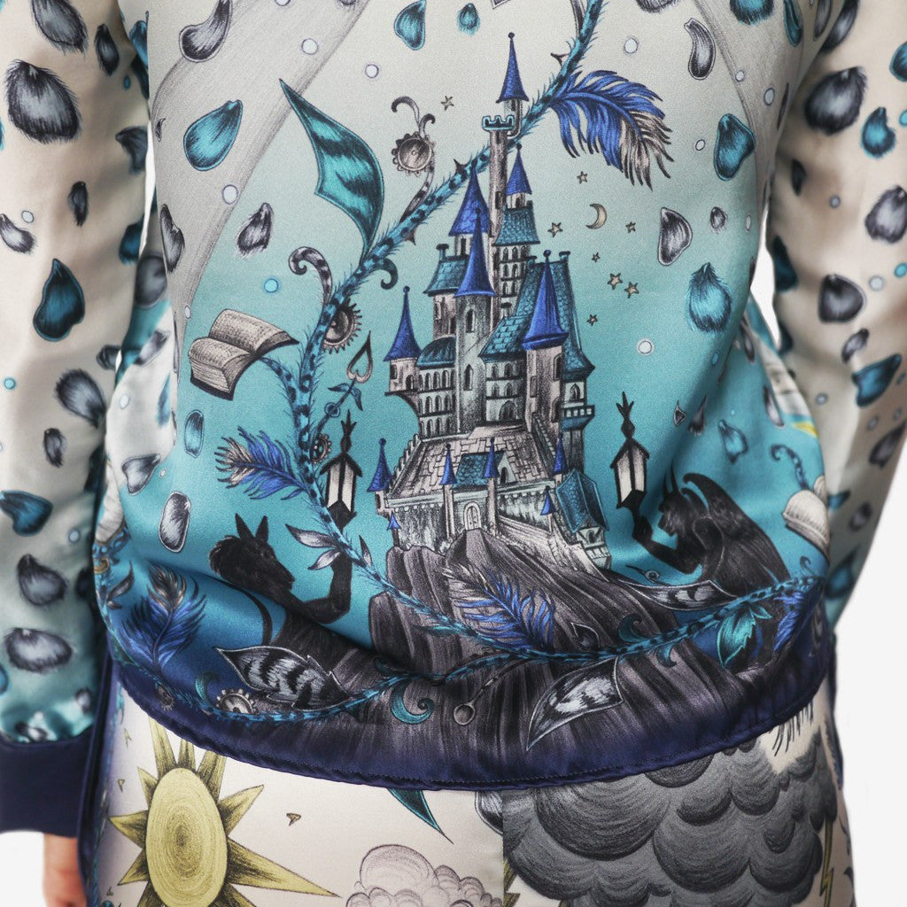 A worn shot of the Emma J Shipley Beauty and the Beast Silk Pyjama Set in Blue, complete with the signature motifs from the classic Disney film.