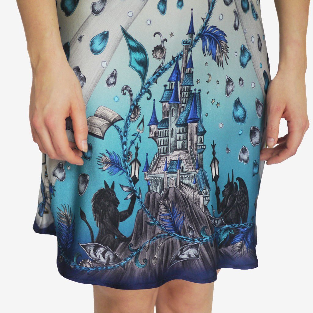 The blue Beauty and the Beast Silk Slip Dress by luxury designer and illustrator by Emma J Shipley is adorned with hand-drawn Disney imagery.