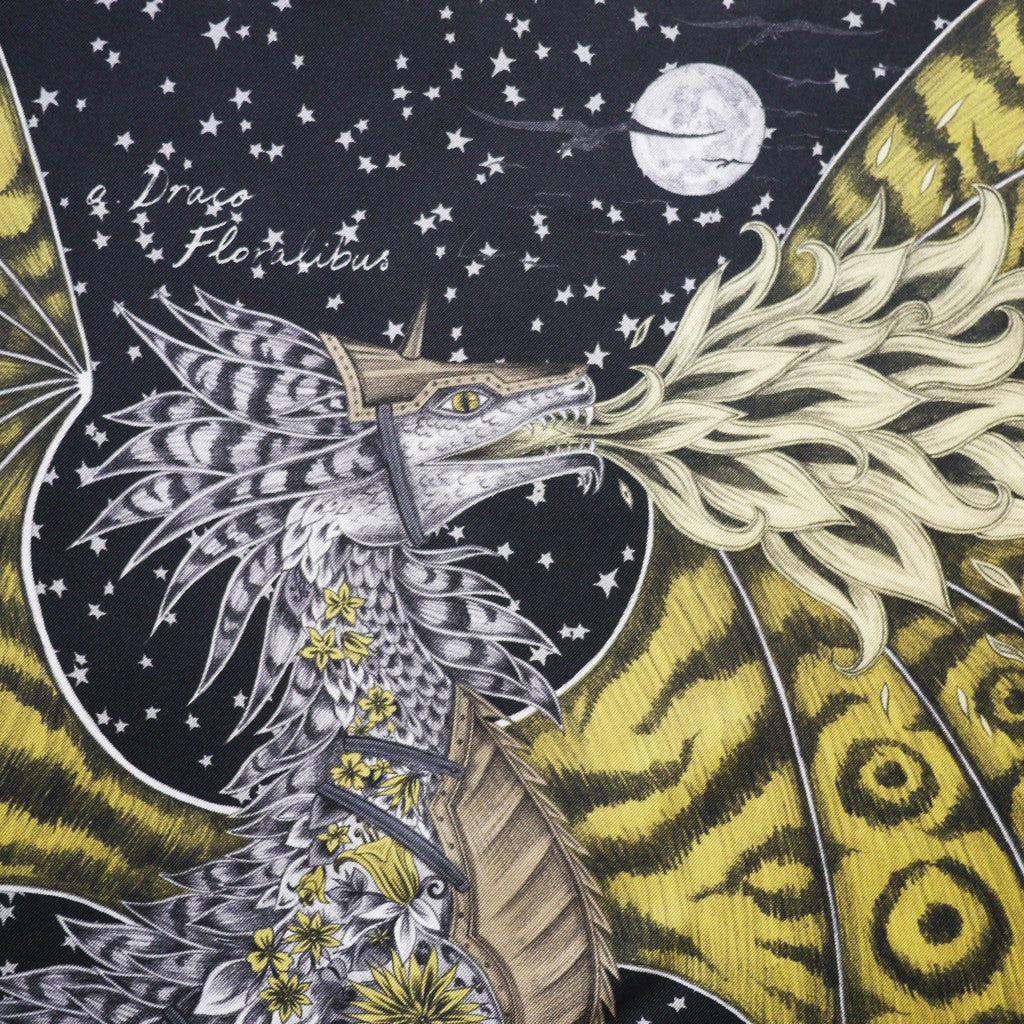 The hand-drawn Drakon features a body made form flowers and foliage, breathing dramatic yellow fire.