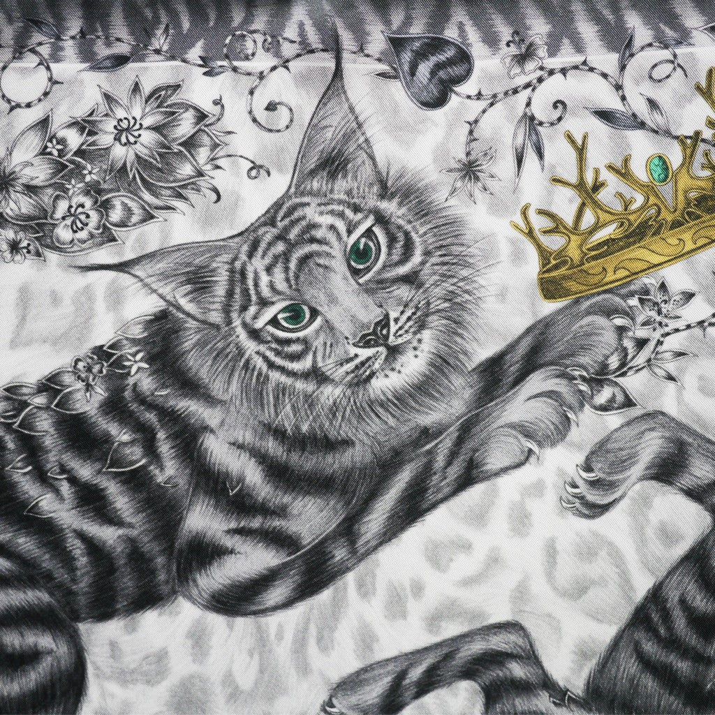 The 60x60cm scarf features two shadow cats frolicking amongst crowns and keys, drawn by Emma J Shipley.
