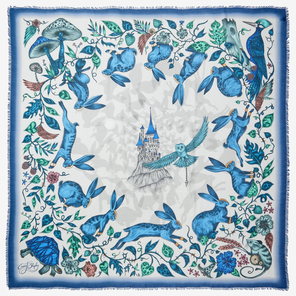 The whimsical blue Frith Modal blend Scarf designed by Emma J Shipley, featuring racing rabbits encircling a magical castle