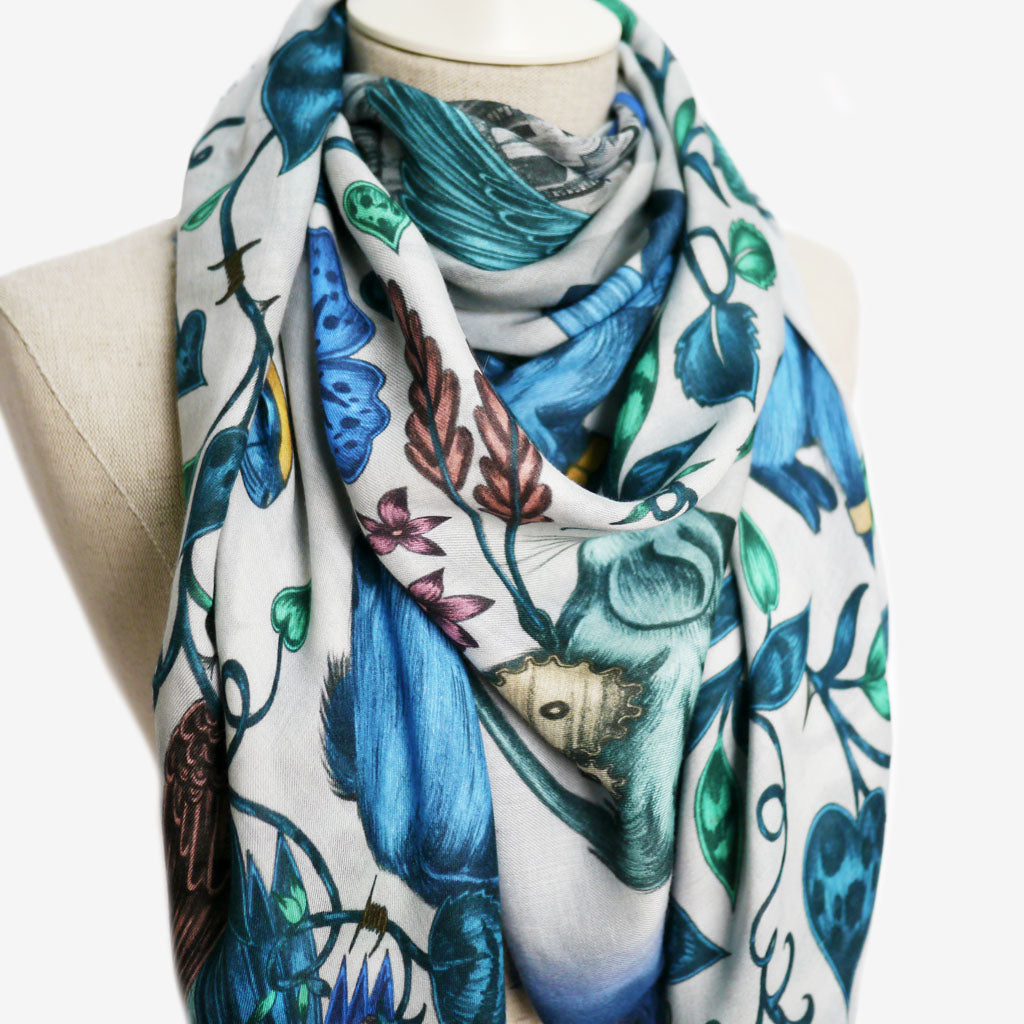 Details from the brilliant blue modal blend scarf designed by Emma J Shipley, featuring an imaginative scene of spotted rabbits encircling a magical castle