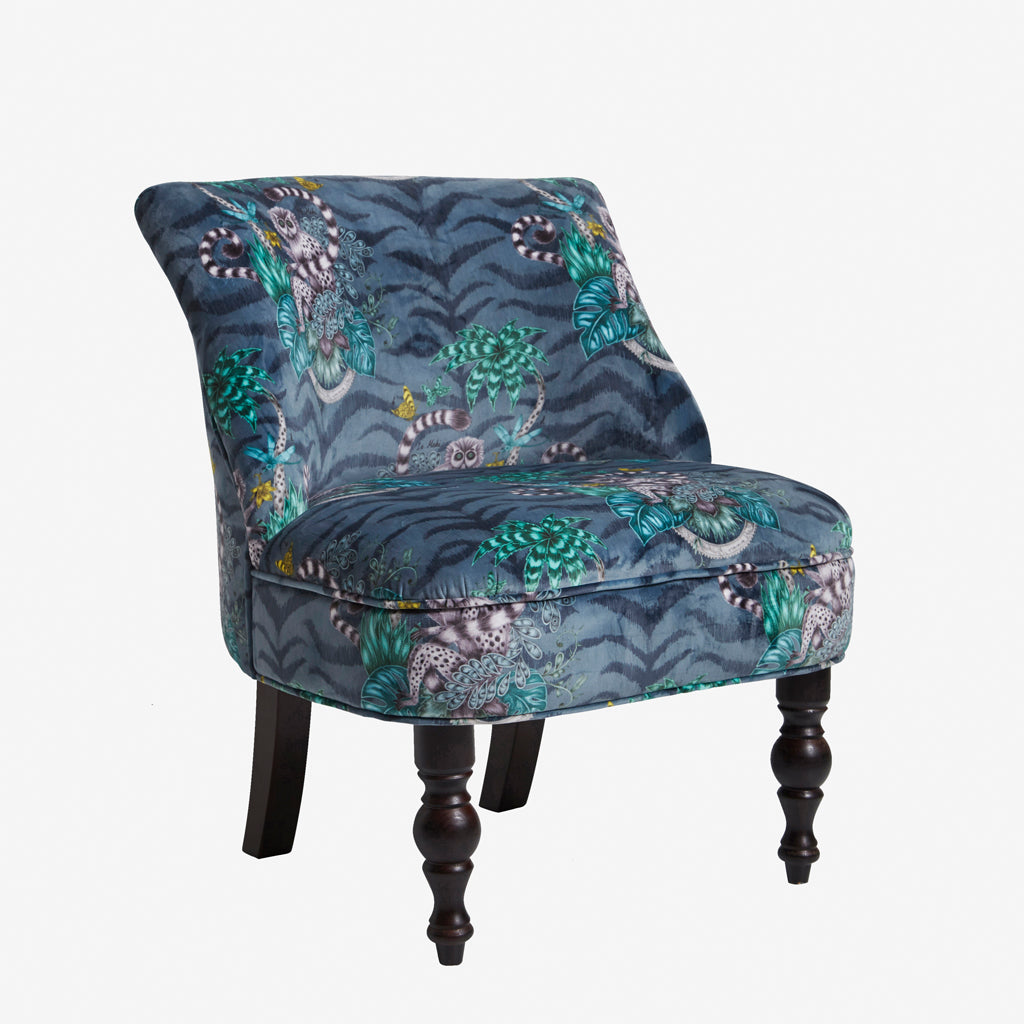 The navy velvet Lemur Langley Chair by Emma J Shipley for Clarke & Clarke is a stunning occasional upholstered chair. Featuring lemurs and a jungle scene