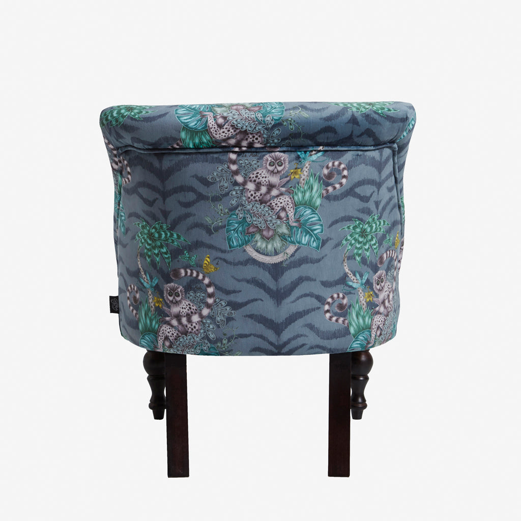The striking velvet Lemur Langley Chair designed by Emma J Shipley for Clarke & Clarke is a beautiful navy and green and blue upholstered chair with our Animalia fabric