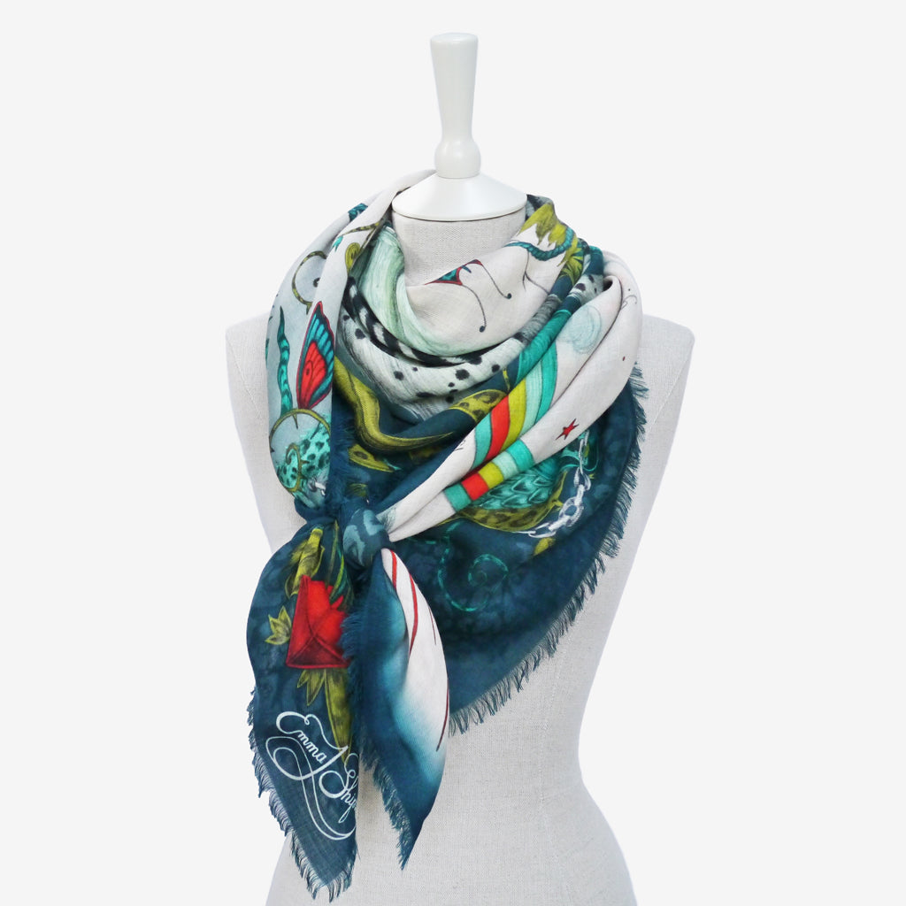 an example of how the Lost World fine wool scarf in the Lime colourway can be worn in a chic, knotted style.