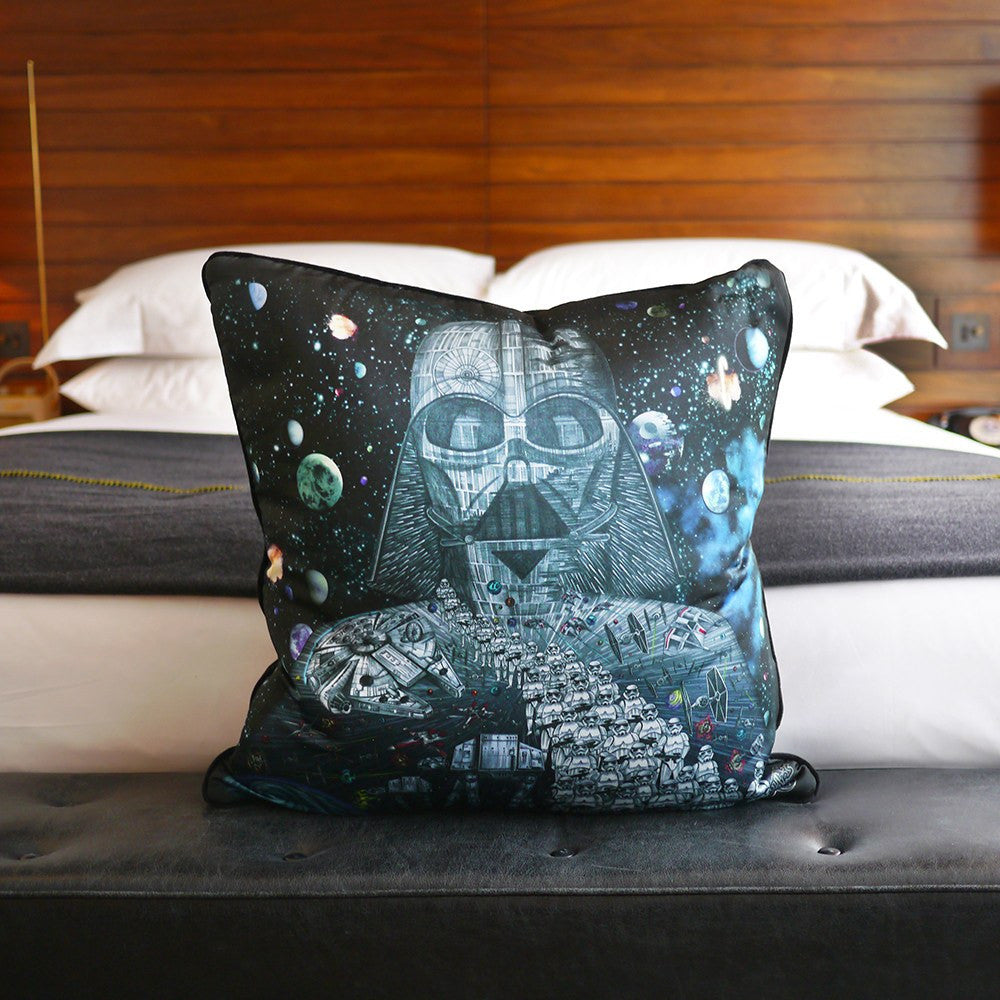 A lifestyle shot of the Emma J Shipley silk and cotton printed Vader Star Wars Cushion in Black.