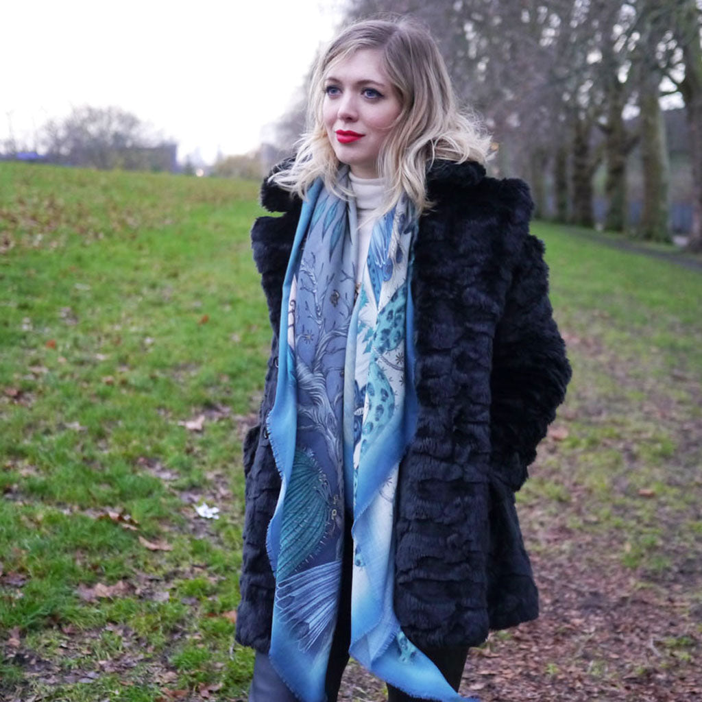 Emma J Shipley the designer wears her Frontier wool luxury scarf featuring owls and eagles in blue colours