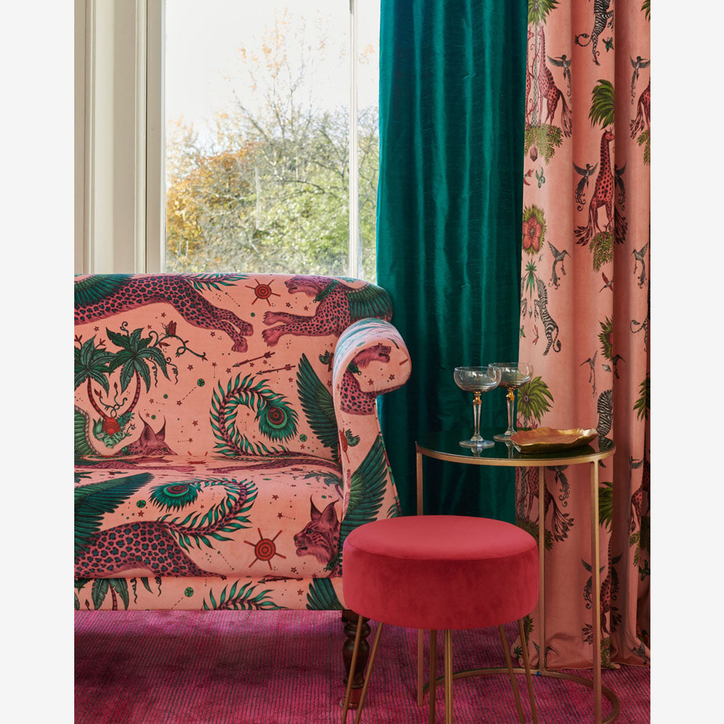 A magical sofa upholstered in Lynx Pink Velvet along with curtains made from the Widerie Sylph Silk Fabric in the Tropic tone, paired with the Pink Creatura, Designed by Emma J Shipley and Made with Clarke & Clarke