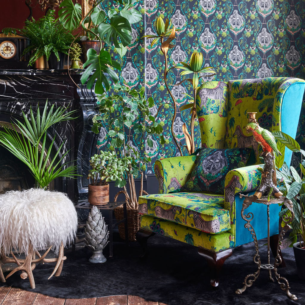 A chair with a cushion covered in the silverback grey velvet along with other products such as the Grey Silverback Wallpaper and a chair in the Lime Lost World Lime Velvet from the Emma J Shipley Wilderie Collection made with Clarke & Clarke