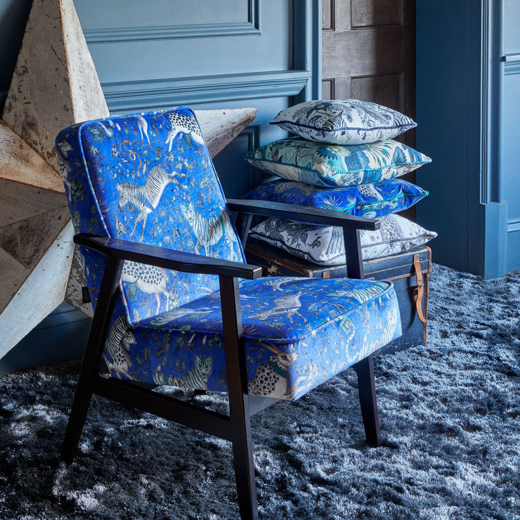 A chair and cushion both covered in the Protea Blue Velvet as part of the Wilderie Collection with Clarke & Clarke by Emma J Shipley