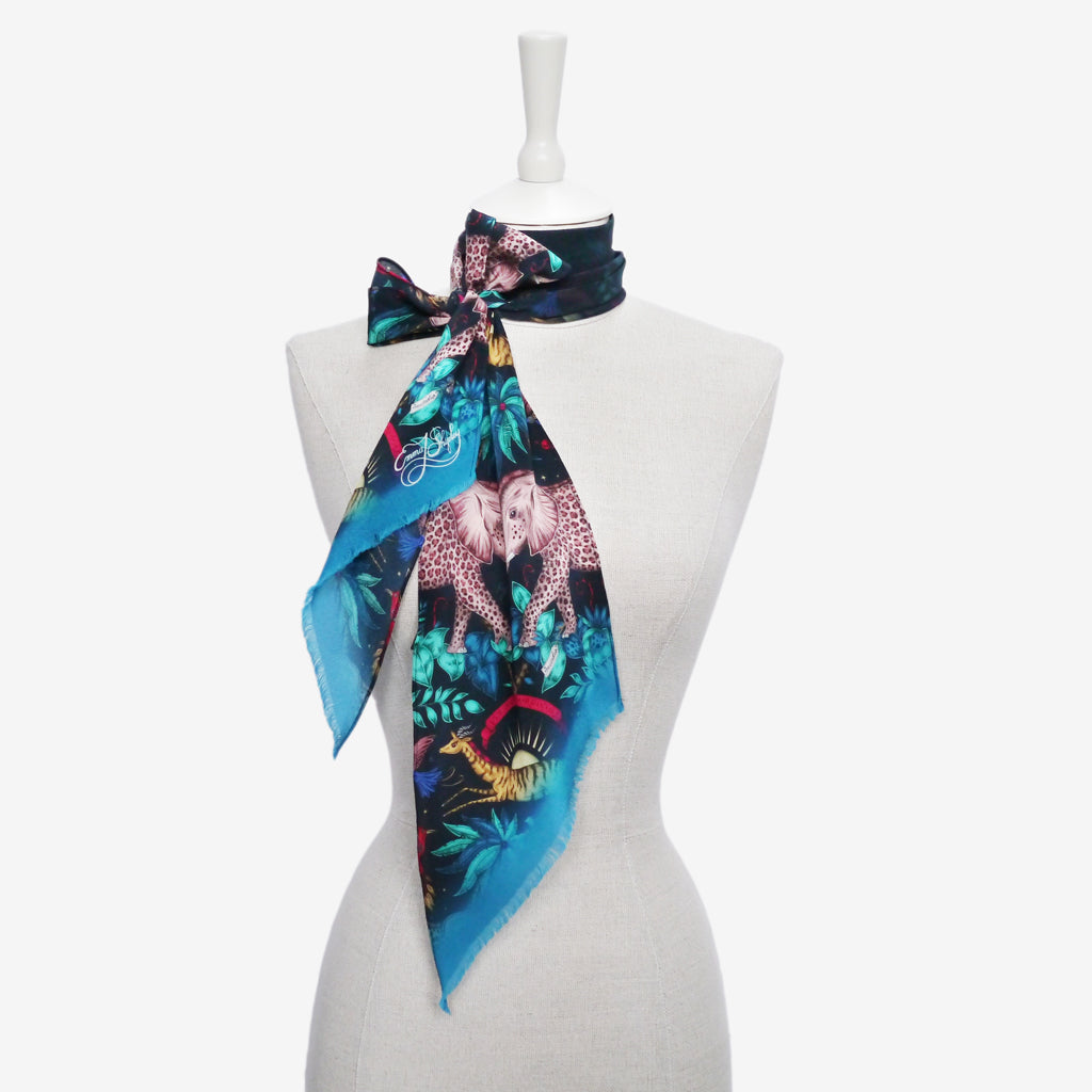 this example of how to wear the Zambezi silk skinny scarf demonstrates a cute but chic bow style and shows off the vibrant technicolour of the design
