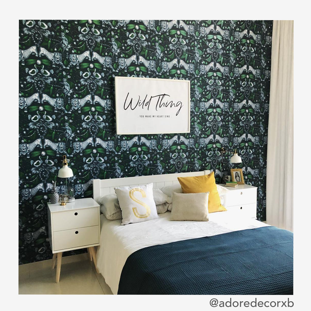The extinct wallpaper from the Animalia collection designed by Emma J Shipley for Clarke & Clarke in use as a bedroom feature wall