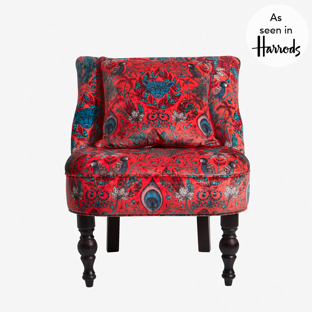 A bold, luxurious upholstered occasion chair featuring Animalia fabric in the Amazon design by Emma J Shipley designed in collaboration with Clarke & Clarke. Featuring a selection of jungle animals in reds and teals