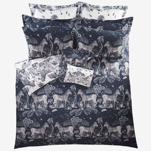 Transform your bedroom into a surreal African landscape with the Lost World Duvet Cover in navy, designed by Emma J Shipley. Featuring a striking scene of creatures including striking Peacock tailed Zebras, Palm trees and parachutes.