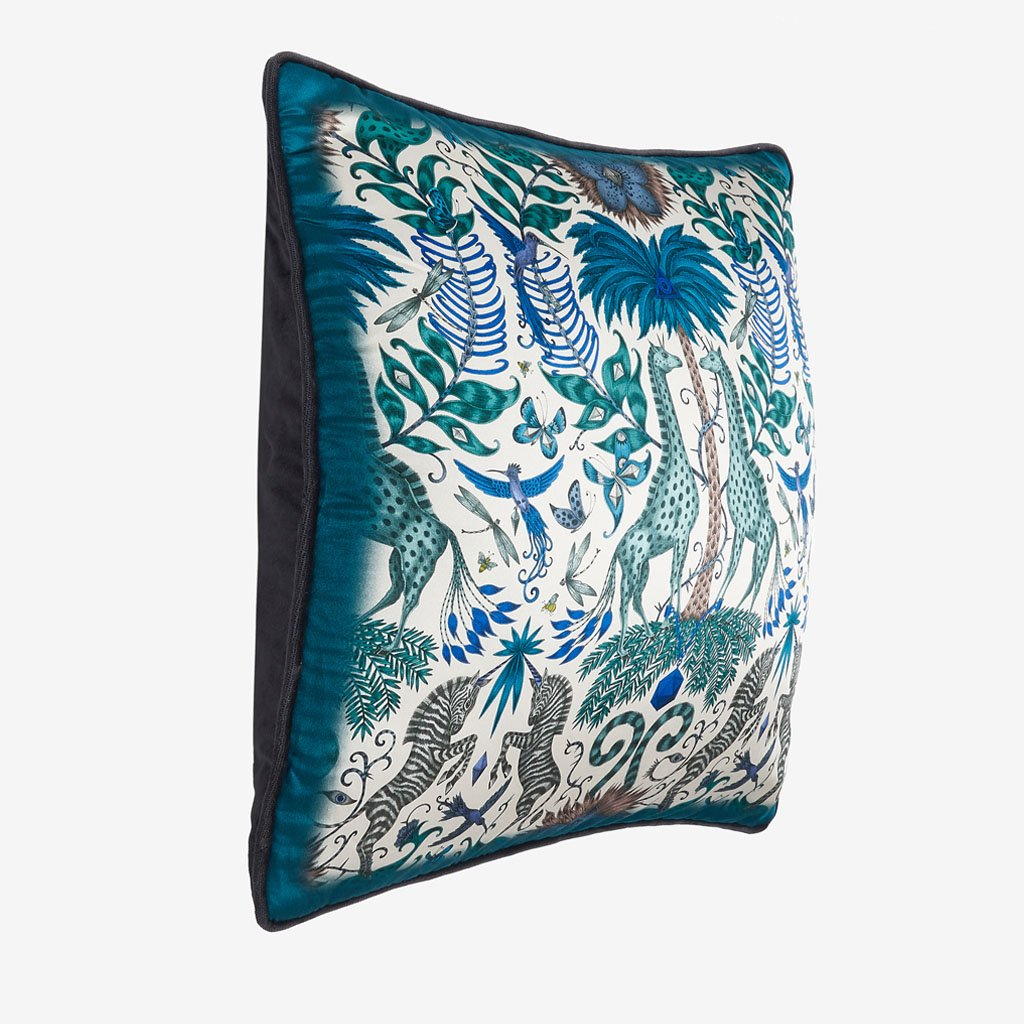 Kruger II square cushion in a striking blue colourway featuring an array of giraffes and zabra around a palm tree hand drawn by Emma J Shipley