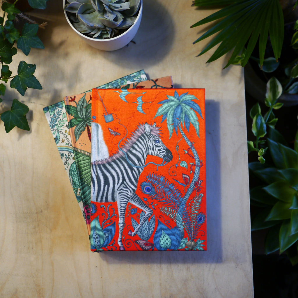 Lifestyle image of the bright Lost World silk notebook featuring a Zebra across the cover - illustrated by Emma J Shipley