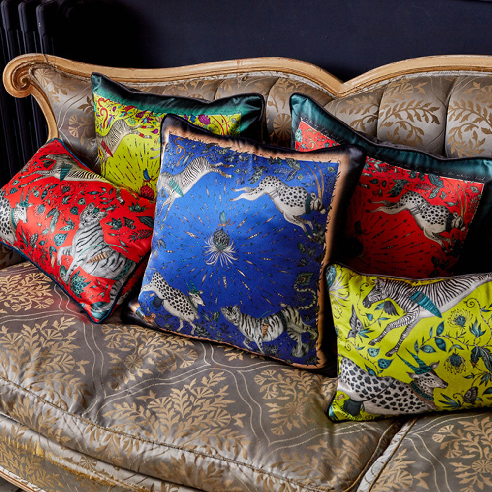 A close up of a sofa adorned with Emma J Shipley Silk cushions including the Red Protea Double Bolster cushion, perfect for layering on a bed or sofa or on their own, they're a magical addition to any home